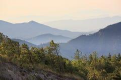 Mistige ochtendzonsopgang met bergachtergrond stock foto