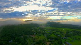 Mistige zonsopgang achter een berg met weelderig landschap stock video