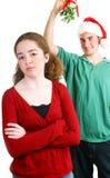 Mistletoe - Girl Not Interested. Hopeful teen boy standing under the mistletoe.  The girl is not interested in him Stock Image