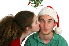 Mistletoe Kiss. A teen girl kissing a surprised looking teen boy under the mistletoe.  Isolated Royalty Free Stock Images