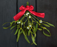 Mistletoe Kisses. Christmas mistletoe with red ribbon bow over dark wood background royalty free stock image