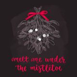 Mistletoe with red ribbon, Christmas and new year decoration with lettering. Holidays hand calligraphy quote with twigs bunch. Vector illustration on chalkboard Royalty Free Stock Photo