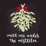 Mistletoe with red ribbon, Christmas and new year decoration with lettering. Holidays hand calligraphy quote with twigs bunch. Vector illustration on chalkboard Royalty Free Stock Image