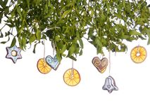 Mistletoe with seasonal decorations. Mistletoe with gingerbread heart cakes and dried orange slice Royalty Free Stock Photos