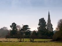 Mistley kristen kyrka som sett från över ett fält med träd in arkivfoton