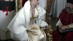 MIstress with beautiful golden dress sits on the carved chair stock footage