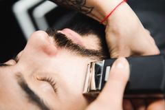 Mistrz ciie włosy i broda mężczyzna w zakładzie fryzjerskim, fryzjer robi fryzurze dla młodego człowieka fotografia stock