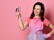 Mistrz w różowych fartucha i medycyny rękawiczkach z instrumentami dla gwoździa salonu w gofrów rożkach szczotkuje, nożyce fotografia royalty free