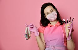 Mistrz w różowych medycyn rękawiczkach i fartuch z gwoździa lakieru próbkami wystawiamy wyposażenie w gofra rożku i robimy maniki zdjęcia royalty free