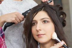 Mistrz wyrządza muśnięcie proszek na twarzy dziewczyna, uzupełnia dnia makijaż w piękno salonie Zdjęcia Royalty Free