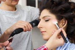 Mistrz wyrządza muśnięcie proszek na twarzy dziewczyna, uzupełnia dnia makijaż w piękno salonie Stylista przy ten czasem Obrazy Royalty Free