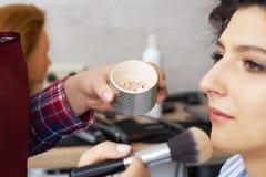 Mistrz wyrządza muśnięcie proszek na twarzy dziewczyna, uzupełnia dnia makijaż w piękno salonie Stylista przy ten czasem Zdjęcia Royalty Free