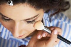 Mistrz wyrządza muśnięcie proszek na twarzy dziewczyna, uzupełnia dnia makijaż w piękno salonie Stylista przy ten czasem Obrazy Stock