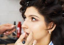 Mistrz wyrządza muśnięcie proszek na twarzy dziewczyna, uzupełnia dnia makijaż w piękno salonie Stylista przy ten czasem Obraz Royalty Free