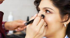 Mistrz wyrządza muśnięcie proszek na twarzy dziewczyna, uzupełnia dnia makijaż w piękno salonie Stylista przy ten czasem Zdjęcia Stock