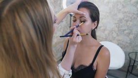 Mistrzowska ` s praca w piękno salonie Makijażu artysta robi up jego klienta, używa mnóstwo palety cienie, różne zbiory