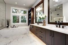 Mistrzowski łazienki wnętrze w luksusowym nowożytnym domu z ciemnymi twarde drzewo gabinetami, białą balią i szkło drzwiową prysz obrazy royalty free