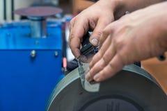 Mistrzowski ostrzenie nóż z czarną rękojeścią dla szlifierskiej maszyny obraz stock