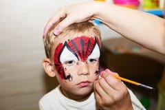 Mistrzowski robi aqua makeup na chłopiec twarzy Obrazy Stock