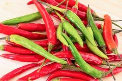 A mistura ajustada de pimentas longas salpica o tempero picante da salsa vegetal de madeira verde vermelha da base do fundo fotos de stock royalty free