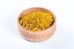 Mistura amarela das especiarias em uma bacia de madeira Imagem de Stock