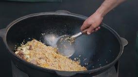 Mistura cozinhando o pilau com a carne em um grande kazan no espaço aberto video estoque