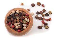 Mistura da pimenta das pimentas quentes, a vermelha, a preta, a branca e a verde em uma bacia de madeira isolada no fundo branco  Fotografia de Stock Royalty Free
