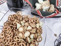 Mistura de biscoitos salgados e de pretzeis dos petiscos na bacia de vidro no fundo branco Feche acima do tiro Fotos de Stock