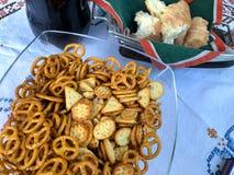 Mistura de biscoitos salgados e de pretzeis dos petiscos na bacia de vidro no fundo branco Feche acima do tiro Foto de Stock Royalty Free