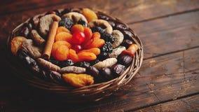Mistura de frutos secados em uma cesta de vime pequena na tabela de madeira filme