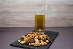 Mistura de frutos secos em uma placa da ardósia, com um vidro da cerveja em um fundo de madeira imagem de stock
