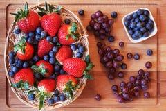Mistura de morangos em uma cesta, em mirtilos e em uva Fotografia de Stock Royalty Free