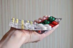 Mistura de tabuletas médicas no bloco, tabuletas embaladas nas bolhas Usou em parte o pacote na palma aberta da mulher fotografia de stock