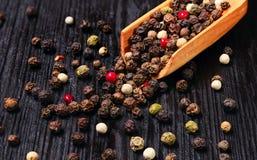 A mistura dos grãos de pimenta dispersou no fundo de madeira Imagens de Stock