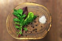 Mistura verde frondosa fresca sobre o fundo de madeira rústico e um punhado do sal e da pimenta preta que encontram-se perto dele Imagens de Stock