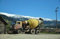 Misturador concreto no fundo de montanhas bonitas imagens de stock
