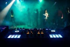 Misturador da música na cabine do DJ no clube noturno com os povos no salão de baile e na atmosfera da noite fotografia de stock royalty free