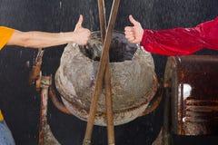 Dois polegares da mostra dos trabalhadores acima na frente do misturador de cimento Imagem de Stock