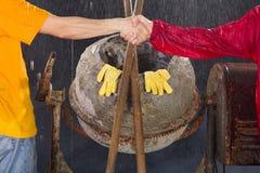 Dois trabalhadores agitam suas mãos na frente do misturador de cimento. Foto de Stock