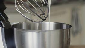 Misturador elétrico que está sendo usado para misturar o creme e a massa vídeos de arquivo