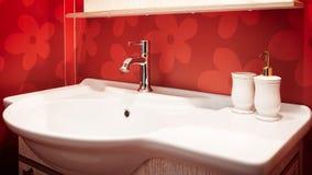 Misturador moderno luxuoso do torneira do estilo em um dissipador branco em um banheiro vermelho bonito Foto de Stock