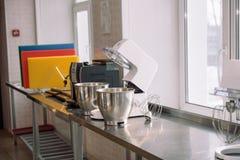 Misturador para chicotear Dispositivo para misturar produtos Cozinhe bolos Misturador do metal na tabela Aprenda cozinhar queques fotos de stock