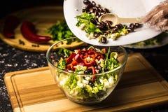 Misturando os ingredientes da salada do feijão preto, da alface, dos ovos e da pimenta doce em uma bacia de vidro fotos de stock royalty free