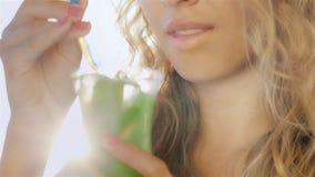 Misturas alcoólicas do cocktail da jovem mulher Na imagem, vista seus mãos e bordos bonitos em um sorriso filme