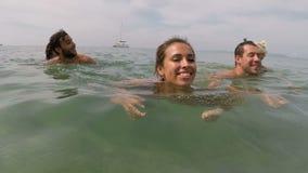 Misture a natação do grupo dos povos da raça em turistas novos do ponto de vista da câmera da ação do mar junto na água filme