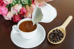 Misture o leite em uma xícara de café Foto de Stock