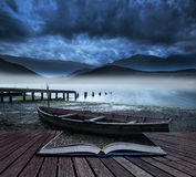 Η παλαιά βάρκα έννοιας βιβλίων στη λίμνη της ακτής με τη misty λίμνη και τοποθετεί Στοκ Εικόνα