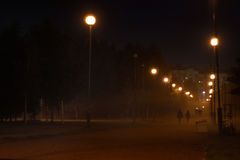 Misty alley, lighted lamps, receding into the distance couple holding hands Stock Images