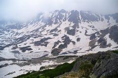 Misty alpine view. Mountains on fog, frozen lake on springtime Royalty Free Stock Photo