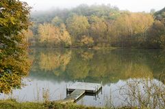 A misty autumn morning. Reflections of fall foliage on a quiet river (Monongahela) on a misty morning. Mist is causing a painterly effect in the trees. Focus on Royalty Free Stock Photos